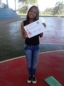 Aluna da equipe 704 Paloma recebendo um certificado de honra ao mérito pela conquista